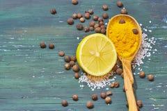 在一把木匙子的姜黄 柠檬,盐 免版税库存图片