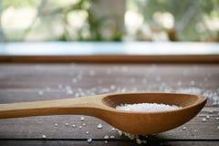 在一把木匙子的海盐在桌上,侧视图 图库摄影