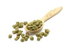 在一把木匙子的被颗粒化的绿色蛇麻草 免版税库存图片