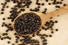 在一把木匙子的黑胡椒豌豆在一张木桌上 图库摄影