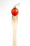 在一把木叉子,白色背景的一点红色新鲜的蕃茄 免版税库存照片