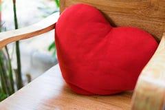 在一把木椅子安置的红色心脏在一个浪漫庭院在m 免版税库存照片