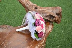在一把木椅子的新娘花束在草 免版税库存照片