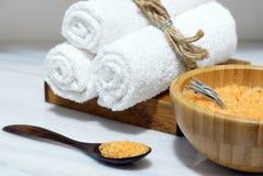 在一把木碗的橙色腌制槽用食盐和匙子和三块白色毛巾在一个木箱在一张白色大理石桌上 免版税库存照片