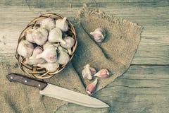 在一把柳条筐和不锈钢刀子的成熟大蒜在木头 库存照片