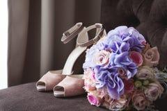 在一把棕色扶手椅子的裸体米黄婚礼鞋子 花束新娘新娘新郎现有量 免版税库存图片