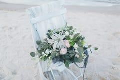 在一把椅子的婚礼花束在海滨 免版税库存图片