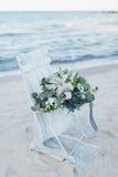 在一把椅子的婚礼花束在海滨 免版税库存照片