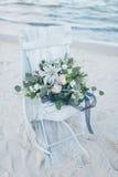 在一把椅子的婚礼花束在海滨 免版税图库摄影