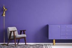 在一把灰色扶手椅子附近的金黄灯和si的紫外碗柜 库存图片