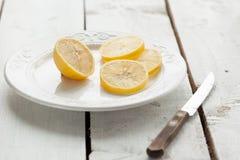 在一把牌照和刀子的柠檬在木表 库存照片