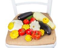 在一把白色椅子的不同的菜从麻袋布 免版税库存照片
