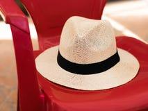在一把红色塑料椅子的草帽 库存图片