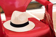 在一把红色塑料椅子的草帽 免版税图库摄影