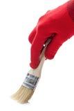 在一把红色手套和油漆刷的手 免版税图库摄影