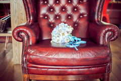 在一把红色扶手椅子的新娘的花束 库存照片