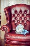 在一把红色扶手椅子的新娘的花束 库存图片