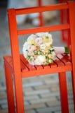 在一把红色椅子的婚礼花束 免版税库存图片