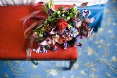 在一把红色椅子的美丽的婚礼花束 免版税库存照片