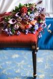 在一把红色椅子的美丽的婚礼花束 库存照片