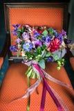 在一把红色椅子的美丽的婚礼花束 库存图片