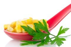 在一把红色陶瓷匙子的罐装玉米 免版税库存图片