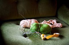 在一把绿色沙发椅子的钩编编织物的工具 图库摄影