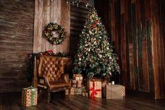在一把老皮革棕色椅子旁边的装饰的圣诞树 黑暗的葡萄酒样式定了调子照片 库存照片