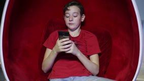 在一把蛋形椅子的青少年的开会与电话 股票视频