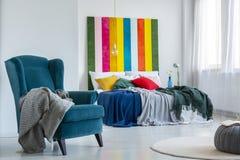 在一把轻松,蓝色扶手椅子的灰色毯子在与坐垫的一张五颜六色的床旁边在与镶边绘画的明亮的卧室内部 免版税库存图片