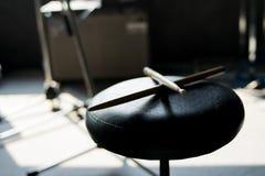 在一把黑椅子的鼓棍子 免版税库存照片