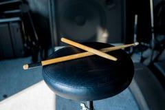 在一把黑椅子的鼓棍子 库存照片