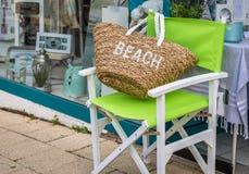 在一把绿色椅子的海滩袋子 免版税库存照片