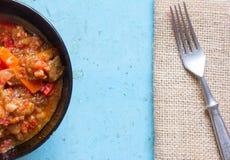 在一把黑色的盘子和叉子的被炖的菜在蓝色背景的席子 图库摄影