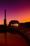 在一排工厂厂房后的五颜六色的日落 免版税库存图片