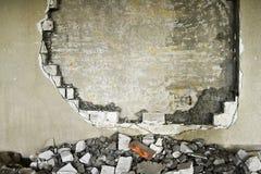 在一排工厂厂房里面的部分地被毁坏的墙壁在爆破下 免版税图库摄影
