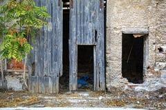 在一排老工厂厂房的残破的滑的木门 库存图片