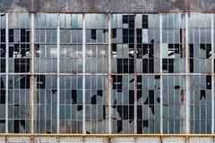 在一排老被放弃的工厂厂房的残破的窗口 库存照片