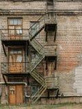 在一排被放弃的工厂厂房的老生锈的防火梯 库存照片