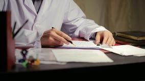 在一支白色实验室外套文字笔的男性手在本文 股票录像