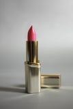 在一支金黄管的桃红色唇膏在灰色背景 库存照片