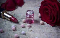 在一支玻璃瓶、红色玫瑰花和唇膏的香水 免版税库存照片