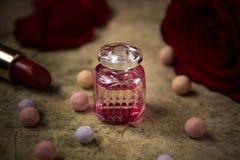 在一支玻璃瓶、红色玫瑰花和唇膏的香水 库存图片