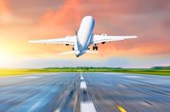 在一明亮的红色日落cloudscape期间,飞机飞行离开在一个跑道机场离开在晚上 库存照片