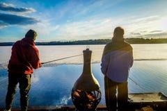 在一晴朗的好天气期间,一条码头捉住的鱼的渔夫 免版税库存图片