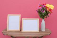 在一木和花的两张照片框架在桃红色背景的瓶子 免版税库存照片