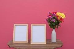 在一木和花的两张照片框架在桃红色背景的瓶子 图库摄影
