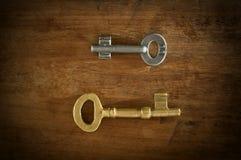 在一木地板loe安置的老两把钥匙锁上光 免版税库存图片