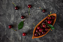 在一木杯的新鲜的樱桃在黑暗的背景 库存图片