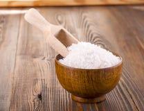在一木杯的白色腌制槽用食盐木表面上 库存照片